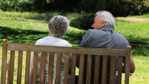 Elderly couple looking at something sitting on a b Footage