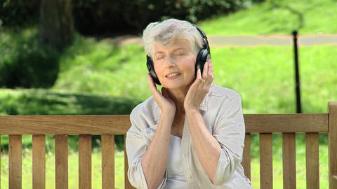 Elderly woman listening to music with headset on a Footage