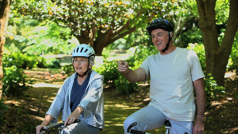 Elderly couple on bikes looking at the way ahead Footage