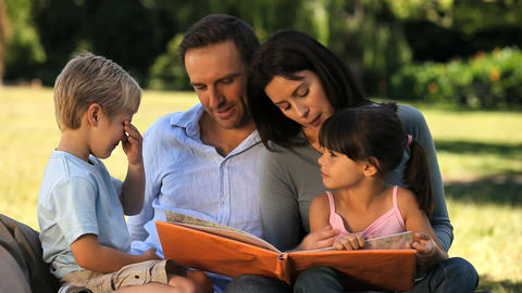 Family looking at a book sitting on the grass Footage