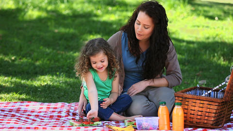 Girl enjoying strawberries with her mother sitting Footage