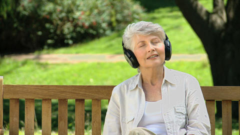 Old female listening to music with headset on a be Footage