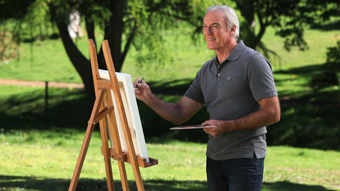 Old male painting a canvas Footage