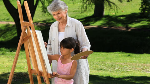 Pretty girl painting a canvas with grandmother Footage