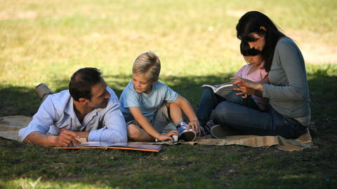 Children doing homework with parents on the grass Footage
