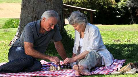 Elderly couple playing chess on a tablecloth Footage