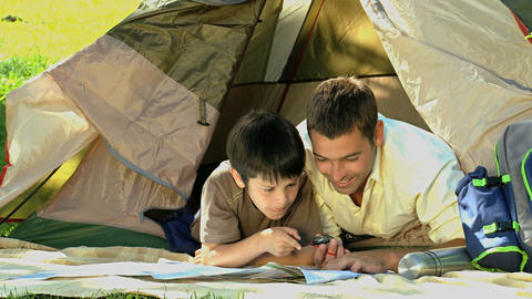 Dad and son looking at a map in front of a tent Footage