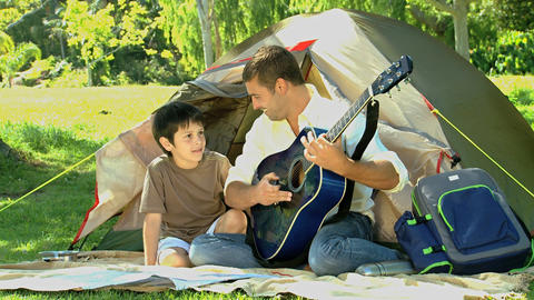 Father playing guitar to his son in front of a ten Footage