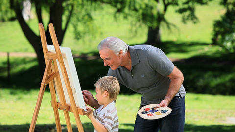 Young boy painting a white canvas with grandad Footage