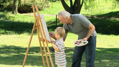 Little boy painting a white canvas with grandfathe Footage