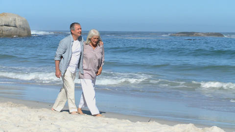 Elderly couple walking along the beach Footage