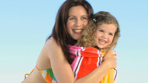 Mother hugging her daughter with a beach towel Footage