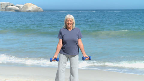 Elderly woman working his muscles with dumbbells Footage