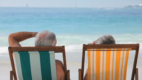 Elderly couple looking at the ocean sitting on bea Footage