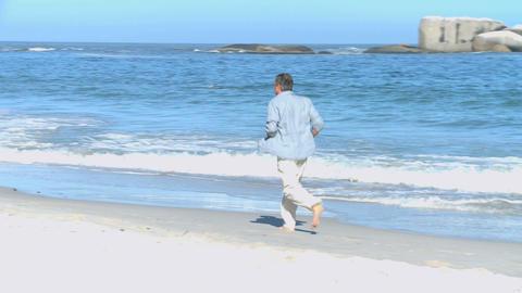Man running along the beach Footage