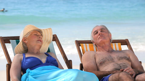 Aged couple relaxing on beach chairs Footage