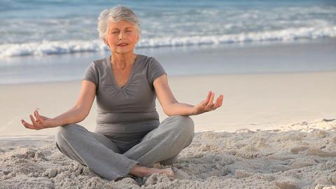 Aged woman doing yoga Footage