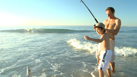 Man fishing with his son on the beach Footage
