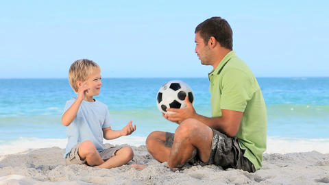 Boy and his father playing with a soccer ball Footage