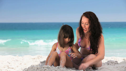 Mother playing with her daughter on the sand Footage