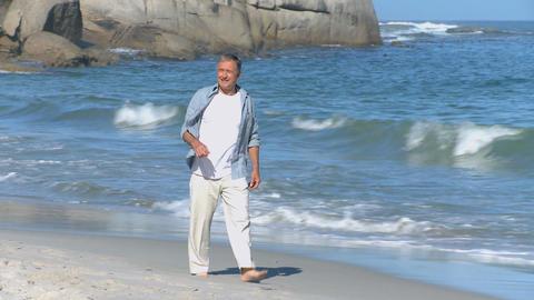 Elderly man walking along the beach Footage