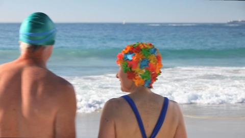 Elderly couple running to the sea Footage