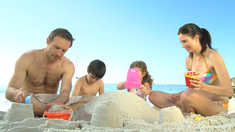 Happy parents building a sand castle with their ch Footage
