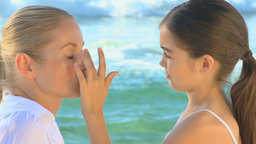Daughter putting suncream on her mother Footage