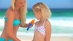 Mother putting suncream on her daughter Footage