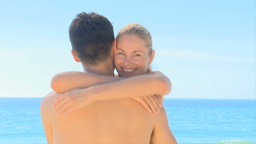 Attractive woman hugging boyfriend on a beach Live Action