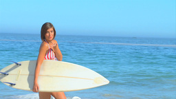 Pretty darkhaired woman posing with her surfboard Footage