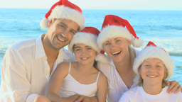 Family wearing Christmas hats on a beach Footage