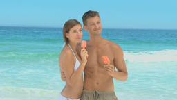 Beautiful couple eating orange water ices Footage