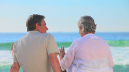 Mature couple sitting talking at the waters edge Footage