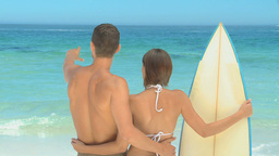 Cute couple with surfboard looking at the sea Footage