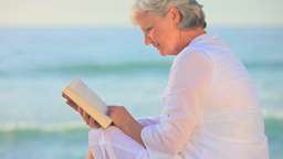 Mature woman sitting reading on a beach Footage