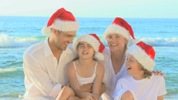 Cute family wearing Christmas hats on the beach Footage
