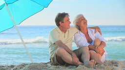 Elderly couple laughing under a beach umbrella Footage