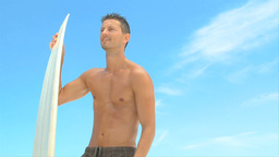 Wellbuilt man getting out of the water after surfi Footage