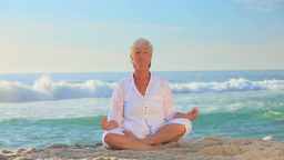 Mature woman in white doing yoga Footage
