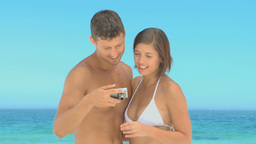 Beautiful couple taking photos on a beach Footage