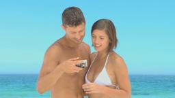 Beautiful couple taking photos on a beach Footage