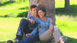 Loving young couple leaning against a tree Footage