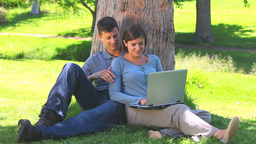 Young couple with a laptop leaning against a tree Footage