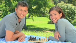 Young couple playing chess while lying on the gras Footage