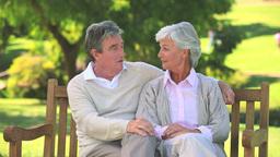 Mature couple talking while walking with their bik Footage
