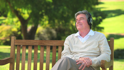 Mature man listening to music with his headphones Footage