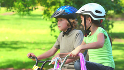 Young girl cycling with her brother Footage
