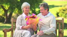 Mature man giving a bunch of flowers to his wife Footage