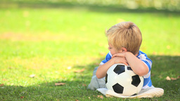 Young boy lying on the grass with his ball Footage